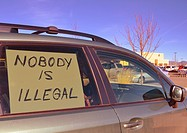 sign in car window, New Mexico (pertaining to immigration policies). A protest.