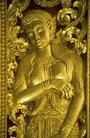 Gilded apsara carving on a temple door at Wat Xieng Thong, Luang Prabang, Laos.