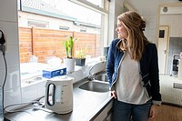 Tilburg, Netherlands. Young caucasian woman relaxing a moment at her kitchen sink after doing some home cleaning.