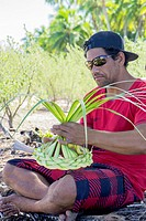 French Polynesian man making a palm hat in Moorea.