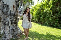 Teenage girl standing by a tree in San Diego, California.