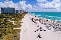 Florida, Miami Beach, sand, Atlantic Ocean, surf, overhead aerial view, lounge chairs, W South Beach, hotel, boardwalk, high rise condominium building...