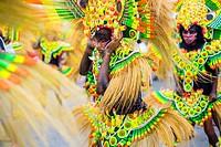 Participants wearing hand made costumes made from natural matirals dance in the street parade at Ati-Atihan festival, Kalibo, Aklan, Western Visayas, ...