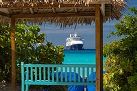"""Shadey bench seat overlooking turqoise waters of Halfmoon Cay and Holland American Cruise Liner """"""""Amsterdam,"""""""" Bahamas."""