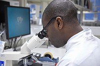 Man in a research laboratory looking through a microscope in the UK