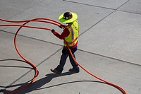 Tucson, Arizona - An electrical worker handles cables in the hot sun at Tucson International Airport.