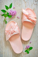 Rose pink woman slippers on wooden background.