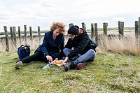 Regte Heide, Netherlands. Young man and woman celebrating easter with a cake, while sitting down on top of a pre-historic barrow.