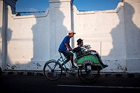 A rickshaw driver carrying customers in the city of Yogyakarta, Java, Indonesia.
