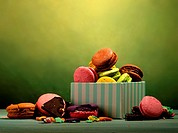 Assortment of macarons in gift box on green background.