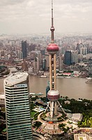 Shanghai visible beyond the Huangpo, with the Oriental Pearl Radio and TV Tower, Pudong New Area, in foreground. China.