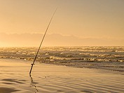 A fishing rod on a support stand - waiting for the bite. Sunrise on the beach. Cape Town, South Africa. . .