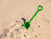 Child´s toy spade digging in the seaside mud at low tide. Cape Town, South Africa.
