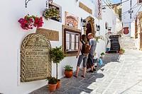 A Couple Look At A Menu Outside The Calypso Restaurant, Lindos, Rhodes, Greece.