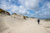 visitor in dunes and blue sky with white clouds at terschelling, holland