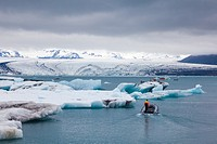 Tour boat operators and patrol boats amid icebergs on the Jokulsarlon glacial lagoon.