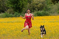 Girl with a red dress running with a dog in a yellow field.