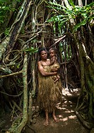 Woman with her baby in traditional skirt standing under a banyan tree, Efate Island, Port Vila, Vanuatu.