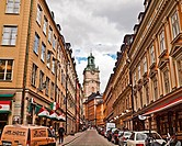 A narrow street in Stockholm with the clock tower of the Church of St. Nicholas (Sankt Nikolai kyrka) also known as Storkyrkan (The Great Church) and ...