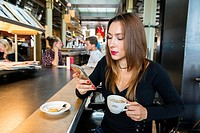Rotterdam, Netherlands. Portrait young adult brunette woman sitting at a cafe´s reading and newspaper table, drinking a cup of coffee and using her sm...
