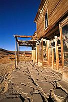 Evening light on cracked sidewalk and the front of the Wheaton and Hollis Hotel on Main Street, Bodie State Historic Park (National Historic Landmark)...