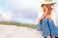 Young woman on sand dune thinking.