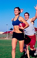 Young woman with football about to be tackled