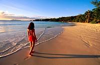 Woman walking on desert beach at sunset. Praslin Island. Seychelles.