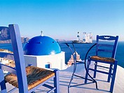 Greece, Cyclades Islands, Santorini, Oia village. Blue dome church. Ouzo & olives at sunset.