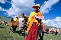 Monk with water melon. Litang Horse Festival. Sichuan. West China