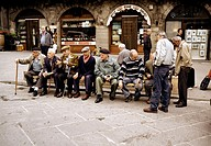 Old men in village of Cortona visiting and chatting. Tuscany. Italy.