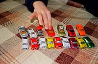 A little boy of 5 years playing with toy cars and cars of chocolate presented to him by his grandmother. While playing, sometimes eats one or two cars...