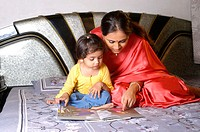 Mother teaching her daughter sitting on a bed.