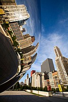 Illinois. Chicago. Cloud Gate sculpture in Millennium Park in early morning, plaza around Bean, stainless steel design, buildings along Michigan Avenu...