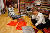 German female tourist negotiating prices for typical indian fabrics in a small boutique in the jewish part of Cochin (Kochi). Cochin, Kerala, India 20...