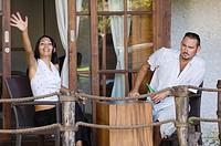 Couple sitting at villa porch and waving
