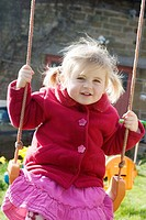 3 year old girl swinging outside, smiling into camera, with bunches