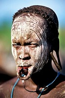 This woman took her plate out of her lower lip. the white ash color covers the face in order to scare rival tribals.