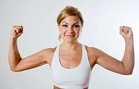 Young blond woman in workout gear happily flexes her muscles.