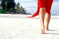 Woman walking along the beach at Unguja Island while only her legs are visible and a part her red skirt, Zanzibar Archipelago, Tanzania, East Africa.