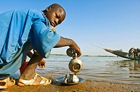 Young man preparing tea by Niger River, Segou, Mali