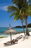 Beach in Mauritius with view over Indian Ocean with shade umbrella and two beach beds