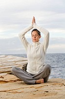 Woman doing yoga in a cliff by the sea