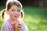 Little girl drinking soda in the garden