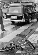 Seventies, black and white photo, traffic, deadly road accident, child had been killed, childs bicycle lies near a cebra crossing, policeman, hearse, ...