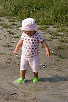 Young girl having fun in a puddle on a warm summer morning  MR