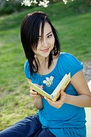 young woman reading book outdoor