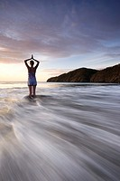 Silhouette of young woman doing yoga at the beach during sunset in Playas del Coco, Costa Rica