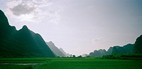 A valley in the Guangxi countryside with the Guilin mountains in China in Asia Far East