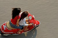 Two fashionable young vietnamese women riding a red Vespa motorbike through the old quarter of Hanoi, Vietnam